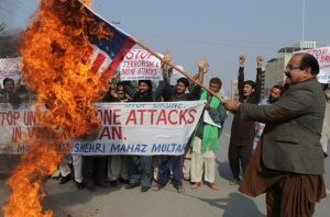 Pakistani protesters burn a representation of the U.S. flag to condemn American drone strikes on militants' hideouts in Pakistani tribal areas, Thursday, Dec. 26, 2013 in Multan, Pakistan. A suspected American drone fired two missiles at a home in a northwestern tribal region bordering Afghanistan, killing several foreign militants, two Pakistani intelligence officials said Thursday. (AP Photo/Mansoor Abbas)